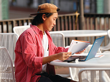 asian male student studying outside golden bear cafe patio